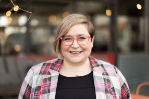 Kate has light hair and eyes. She smiles, looking at the camera. She is wearing a pink plaid coat and pink eyeglasses.