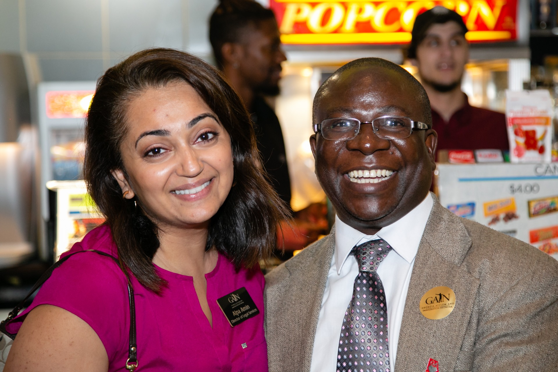 Two people, a South Asian woman and a Black man, stand next to each other, smiling.