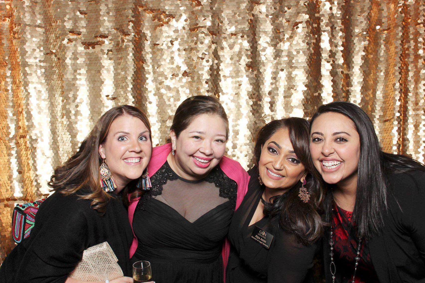 Four women pose, smiling, in front of a gold sequin background.