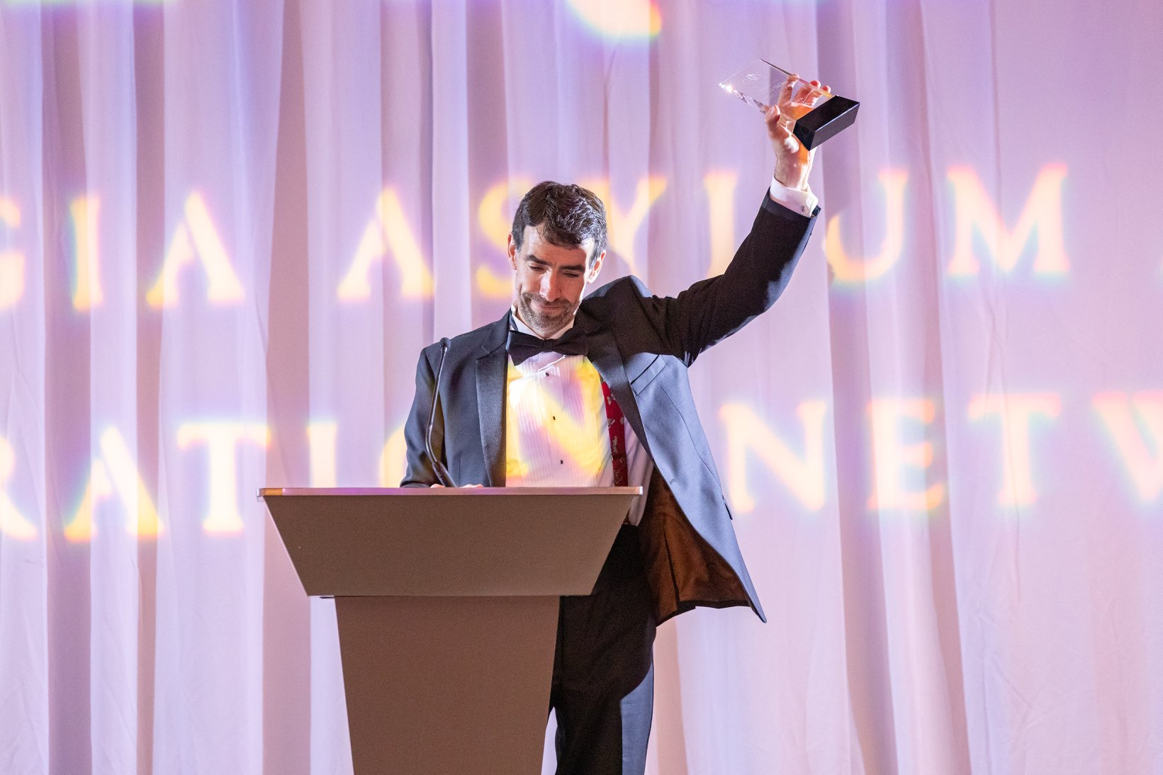 A GAIN honoree stands behind a podium, lifting his award in the air.